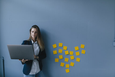 Young businesswoman using laptop with heart shape of sticky notes on the wall - GUSF01723