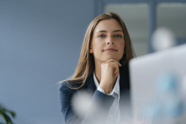 Portrait of a young businesswoman, working in office, using laptop - GUSF01732