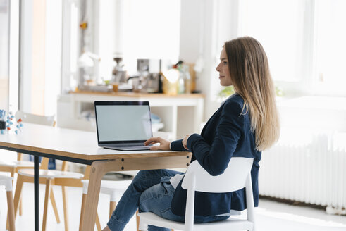 Young businesswoman sitting in office, using laptop - GUSF01735