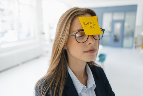 Young businesswman with yellow sticky note on her forehead - GUSF01747