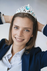 Ambitious young woman wearing crown as an award for her achievments - GUSF01753