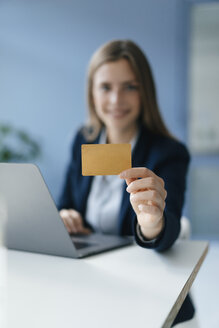 Young businesswoman doing online payment, showing her credit card - GUSF01771