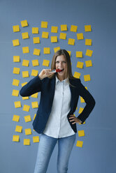 Yong businesswoman standing in front of wall, full of yellow sticky notes, biting marker pen - GUSF01777