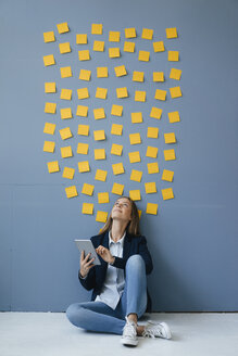 Young businesswoman usig digital tabet, sitting under data cloud - GUSF01780