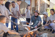 Children and guide roasting twist bread at camp fire - ZEF16086