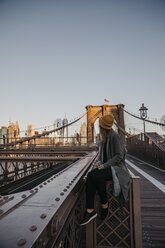 USA, New York, New York City, female tourist sitting on Brooklyn Bridge in the morning light - LHPF00318