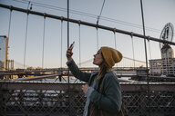 USA, New York, New York City, female tourist using smartphone on Brooklyn Bridge in the morning light - LHPF00321