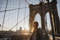 USA, New York, New York City, female tourist on Brooklyn Bridge at sunrise - LHPF00324