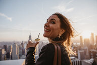 USA, New York, New York City, woman with cocktail glass on viewpoint at sunrise - LHPF00333