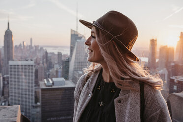 USA, New York, New York City, Portrait of blonde woman with hat at sunrise - LHPF00336