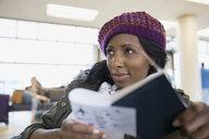 Woman reading book in airport - HEROF03052
