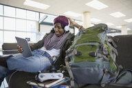 Woman with headphones using digital tablet in airport - HEROF03058