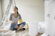 Smiling woman drinking coffee on paint drop cloth - HEROF03064