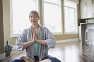 Woman meditating in living room - HEROF03079