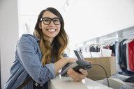 Woman using credit card reader in shop - HEROF03124