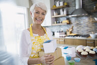 Woman holding boxed cupcakes in kitchen - HEROF03166