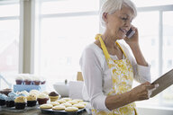Woman on cell phone baking cupcakes in kitchen - HEROF03169
