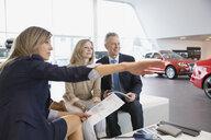 Saleswoman explaining to couple in car dealership showroom - HEROF03172