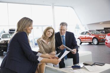 Saleswoman and couple finalizing paperwork in car dealership - HEROF03175