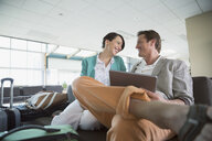 Smiling couple with digital tablet waiting in airport - HEROF03226