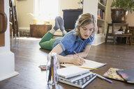 Woman drawing on living room floor - HEROF03244