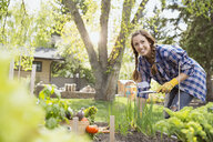 Smiling woman tending to vegetable garden - HEROF03253
