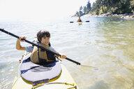 Portrait of boy kayaking in ocean - HEROF03289