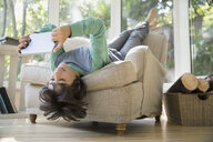 Boy using digital tablet upside-down in armchair - HEROF03313