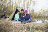 Father reading to daughters at campsite - HEROF03361