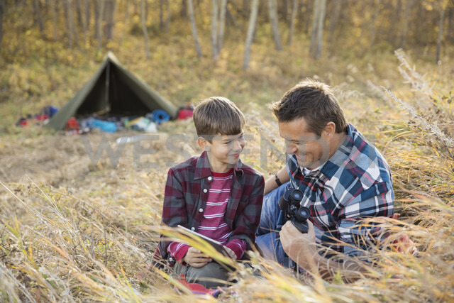 Father and son using digital tablet outside tent - HEROF03364 - Hero Images/Westend61