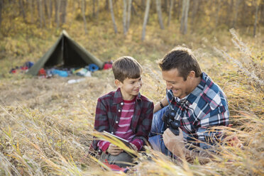 Father and son using digital tablet outside tent - HEROF03364