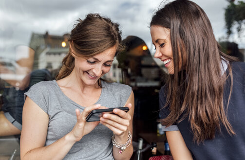 Two women having fun with their smartphone on a terrace - MGOF03881
