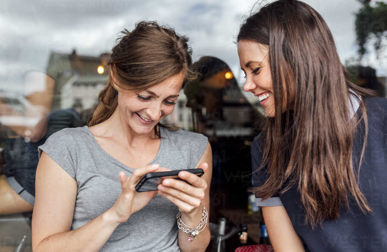 Two women having fun with their smartphone on a terrace - MGOF03881 - Marco Govel/Westend61