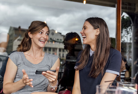 Two women having fun with their smartphone on a terrace - MGOF03884