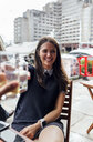 Young beautiful woman toasting with her friends on a terrace - MGOF03887