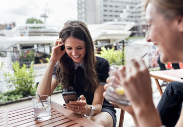 Two happy women with smartphone and drinks on a terrace - MGOF03890