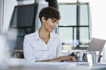 Businesswoman sitting at desk in office using laptop - RBF06852