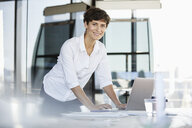 Portrait of confident businesswoman standing at desk in office with laptop - RBF06858
