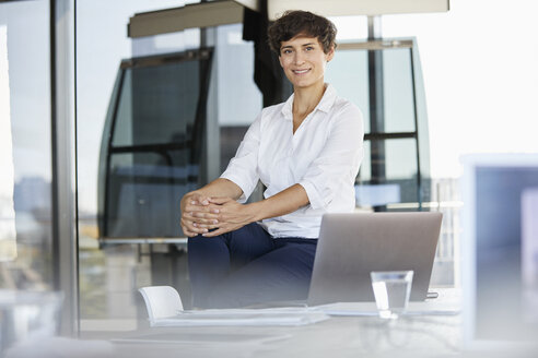 Portrait of confident businesswoman sitting on desk in office with laptop - RBF06861