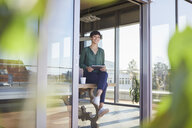 Smiling businesswoman sitting on table with tablet - RBF06864
