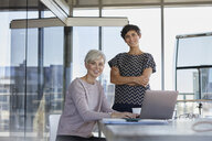 Portrait of two smiling businesswomen with laptop at desk in office - RBF06876