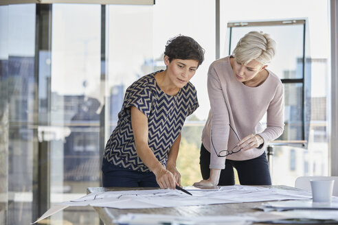 Two businesswomen discussing floor plan on desk in office - RBF06882