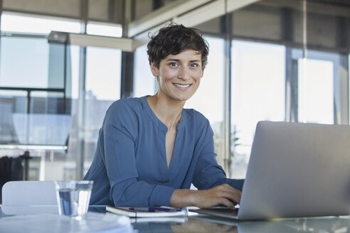 Portrait of confident businesswoman sitting at desk in office with laptop - RBF06885