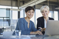Portrait of two smiling businesswomen with laptop at desk in office - RBF06888