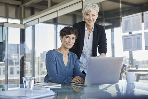 Portrait of two smiling businesswomen with laptop at desk in office - RBF06891