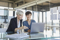 Two smiling businesswomen sharing laptop at desk in office - RBF06894