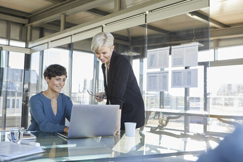 Two smiling businesswomen sharing laptop at desk in office - RBF06897
