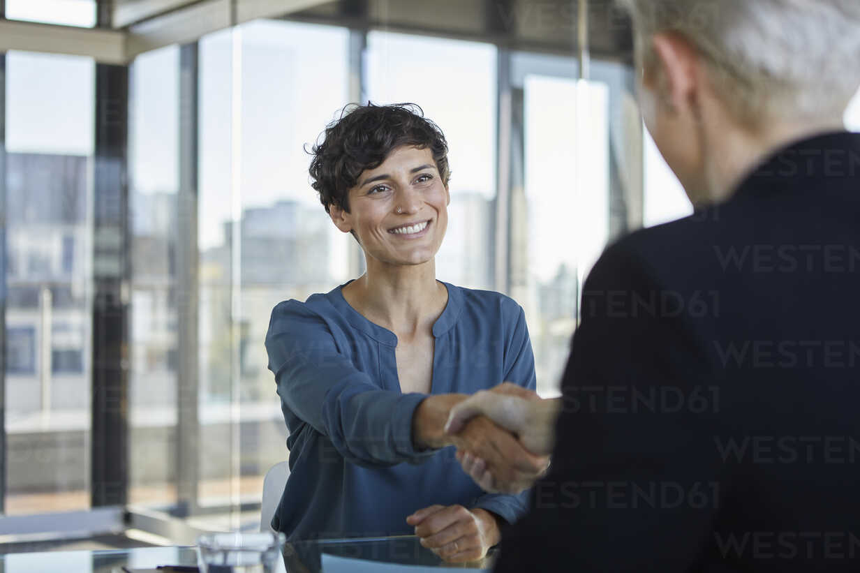 Two businesswomen shaking hands at desk in office - RBF06900 - Rainer Berg/Westend61