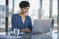 Businesswoman sitting at desk in office using laptop - RBF06903