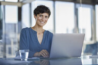 Portrait of confident businesswoman sitting at desk in office with laptop - RBF06906